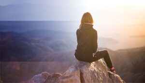 Woman sitting on a peak looking out over a canyon