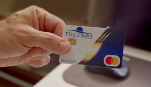 close up of a hand holding a TelComm Rewards credit card